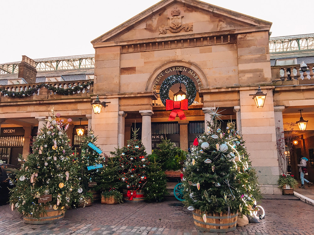 Covent Garden market entrance surrounded by Christmas trees