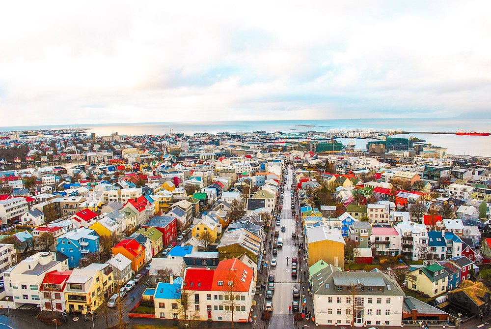 The view of the colourful city roof and sea from the top of the church in Reykjavik