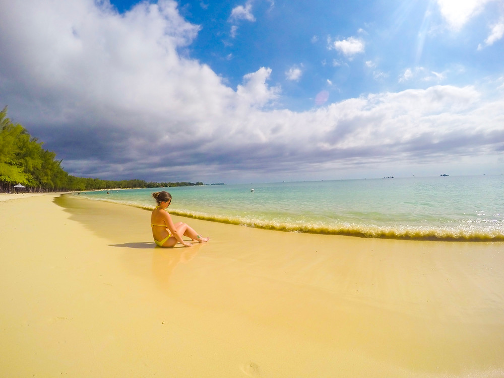 a woman ina yellow bikini sitting on the shore of the beach, wave is approaching. The sky is blue with some rain clouds approaching from the left.