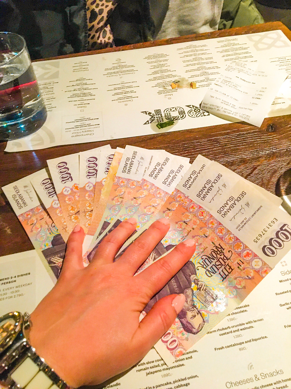 a lot of banknotes on the table hold by a woman's hand, scene in the restaurant