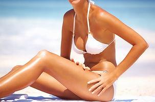 Mulher tomando sol na praia e mostrando o bronzeado