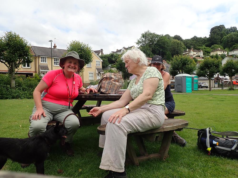 three women and a dog at a picnic table
