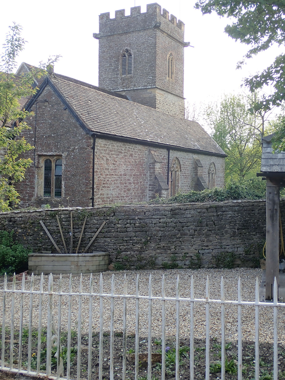 A church with a tower clearly seen from a road.