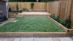 Sleeper retained artificial lawn