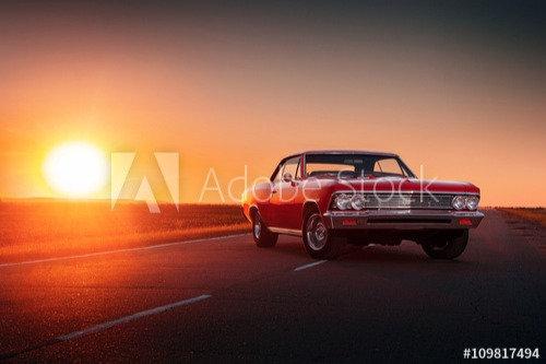 Rode oldtimer bij zonsondergang