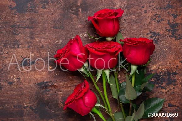 5 rode rozen op houten tafel