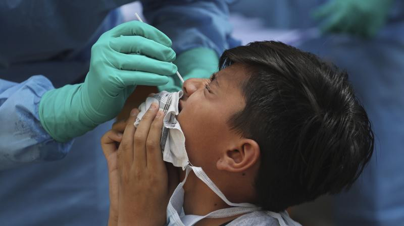 Associated Press photo of a boy in India undergoing a swab test. Source: Asian Age