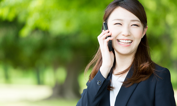 BUSINESS-ASIAN-SMILING-ON-PHONE-IN-PARK_