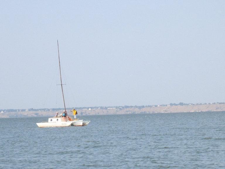 Тримаран плывет мимо крепости