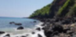 Черные скалы на белом пляже. Бали
