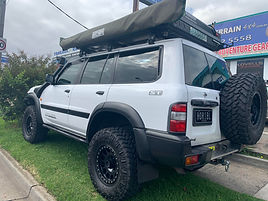 Nissan GU patrol with Bundutop Tent and Tough Touring Ladder mount ostrich wing awning.jpg