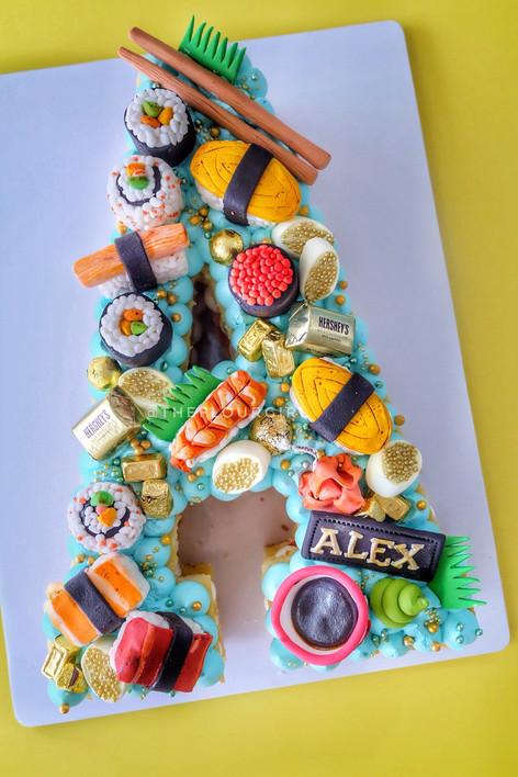 Sushi themed single letter monogram cake