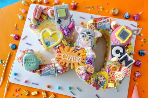90s kid themed multiple number monogram cake
