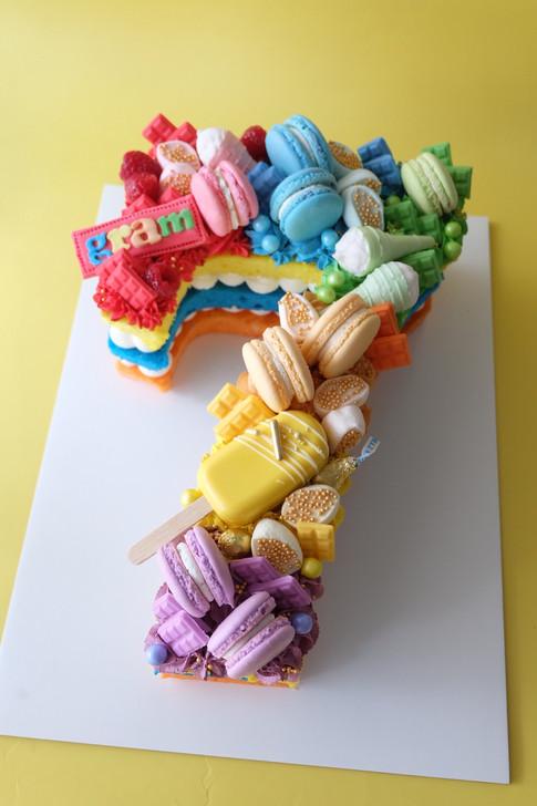 Rainbow themed single number monogram cake