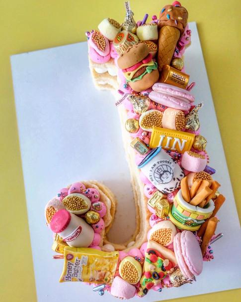Merienda themed single letter monogram cake