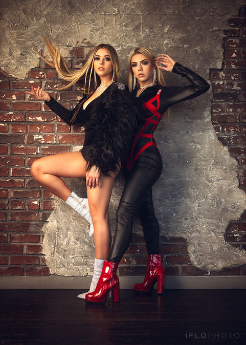 Morgan and Avery wearing stylish bodysuits while posing in front of a brick wall at Gilley's in Dallas, TX.