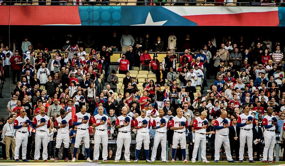 El equipo de Puerto Rico presenta sus respetos al himno nacional de la isla, en la ceremonia protocolar del partido final del Clásico Mundial de Baseball 2017 en el Dodger Stadium de Los Angeles.