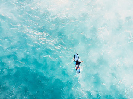 Surfer paddling out into ocean