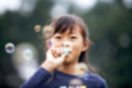 Child with a healthy airway blowing bubbles outside