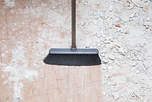 Broom sweeping concrete pieces from floo
