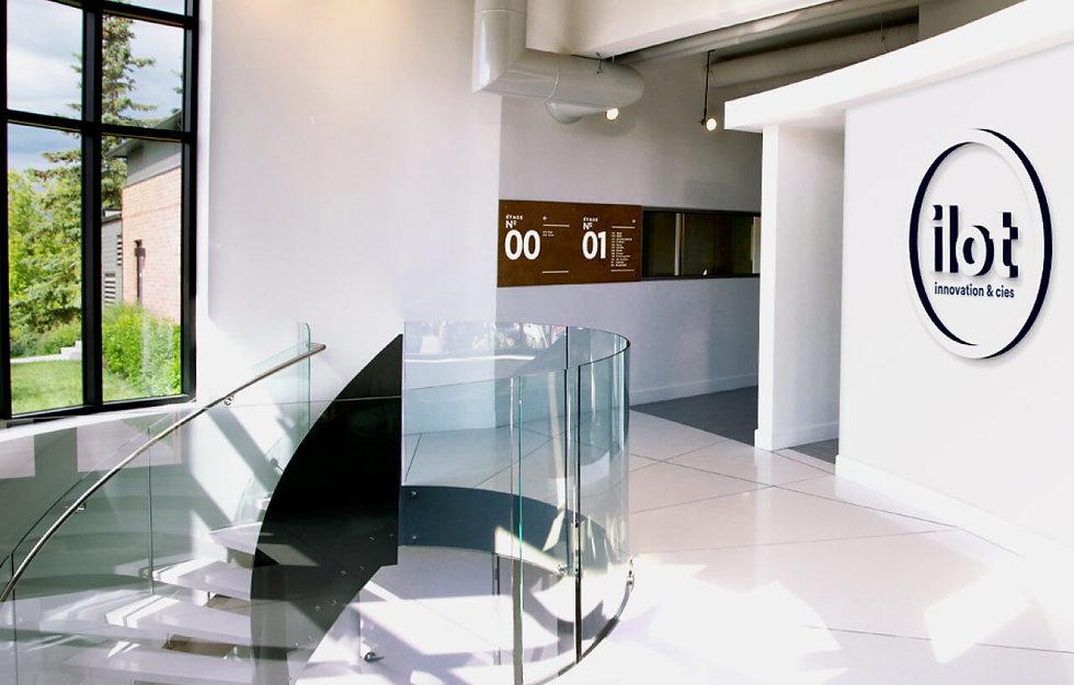 Intérieur de Maverick Analityk avec un escalier en colimaçon et rampe en vitre