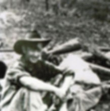Following the battle in PNG's Milak village in 1943, Corporal Tony Gannan is seated next to the foxhole from which his mortar crew caused much devastation on the Japanese advance.