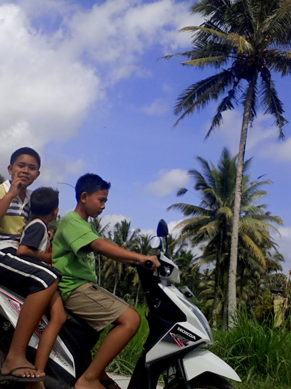 Boys on scooter behind villa