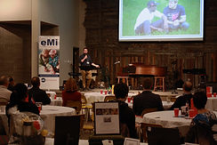 Contribution to Knowledge: Braden Swab speaking about the survey practicum program at an EMI fundraising event