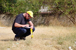 Project Execution: Braden Swab completing a basic survey using a measuring tape in Cambodia