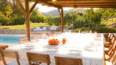 Large shaded table for dining by the swimming pool