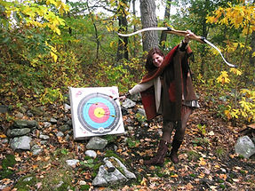 woman in woods next to bullseye target