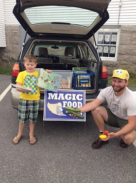 Child and parent picking up books and veggies at Magic Food Bus