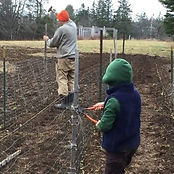 Farmer and child repairing fencing at Old Ackley Farm