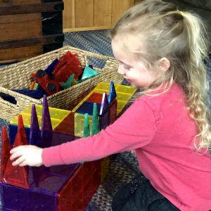 child building castle with magnatiles