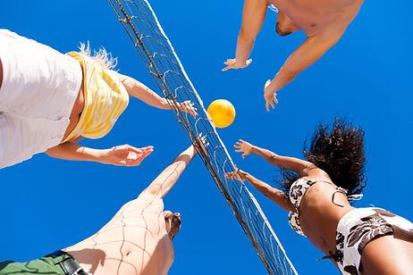 Inquadratura dal basso di quattro ragazzi che si contendono la palla sul filo della rete