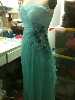 Turquoise blue tulle draped gown with beaded details at waist