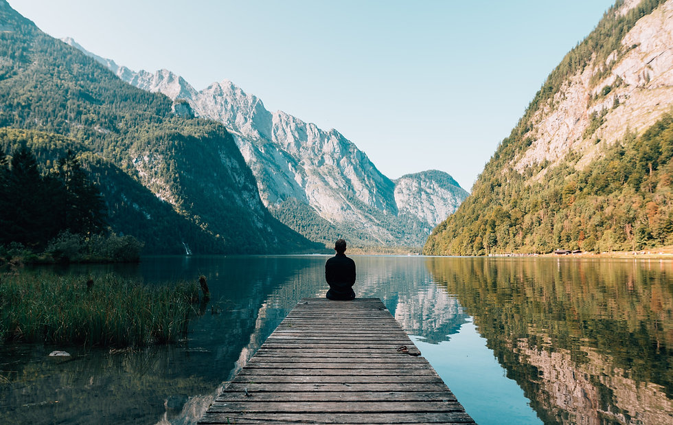 Personne assise devant un lac et de belles montagnes. Sérénité, calme