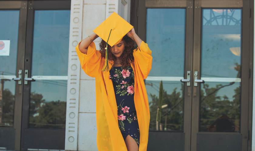 girl in yellow graduation gown preparing to put her cap on