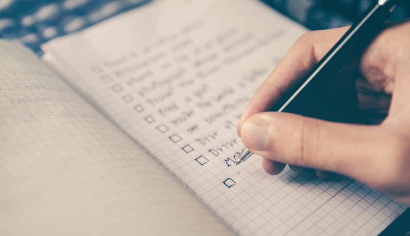 close up of a hand making a checklist in a notebook with a pen