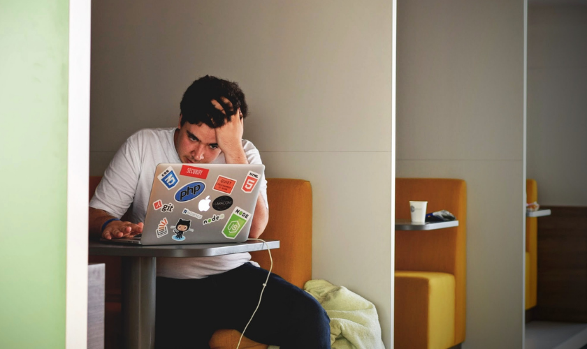 a young man sitting in a restaurant booth working on a laptop looking frustrated
