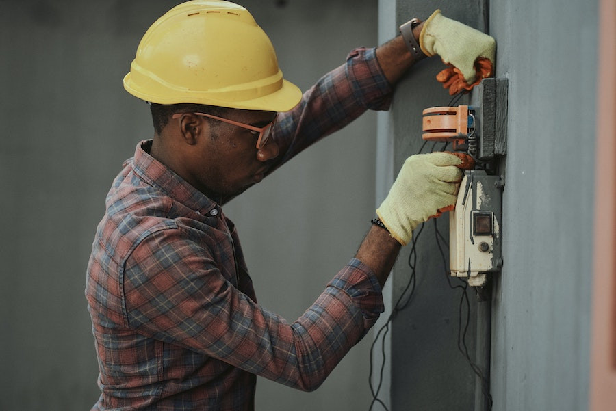 young Black man with a hardhat on using electrician's tools
