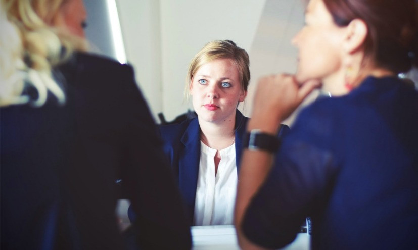 professional woman having conversation with two other women