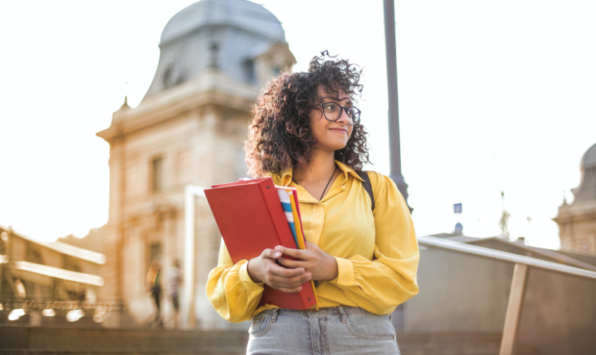 girl in yellow shirt standing in front of college for her first day of school