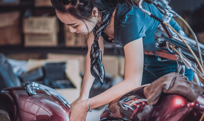 teenage girl working on a motorcycle at auto shop
