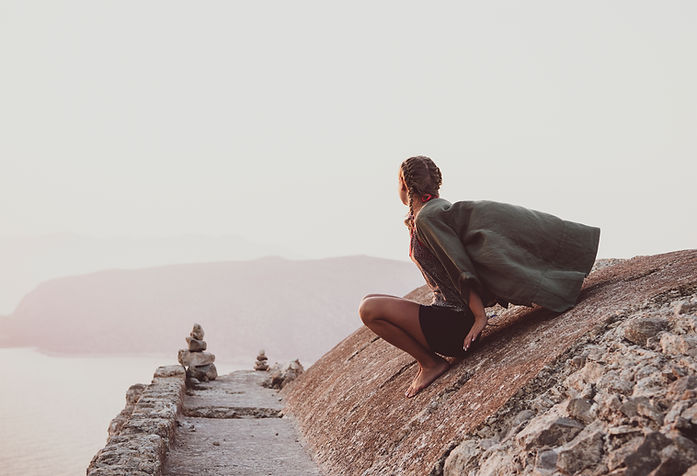 woman-sitting-and-looking-at-horizon-in-