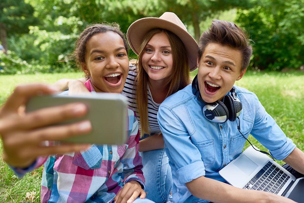 smiling-teenagers-taking-selfie-in-park-