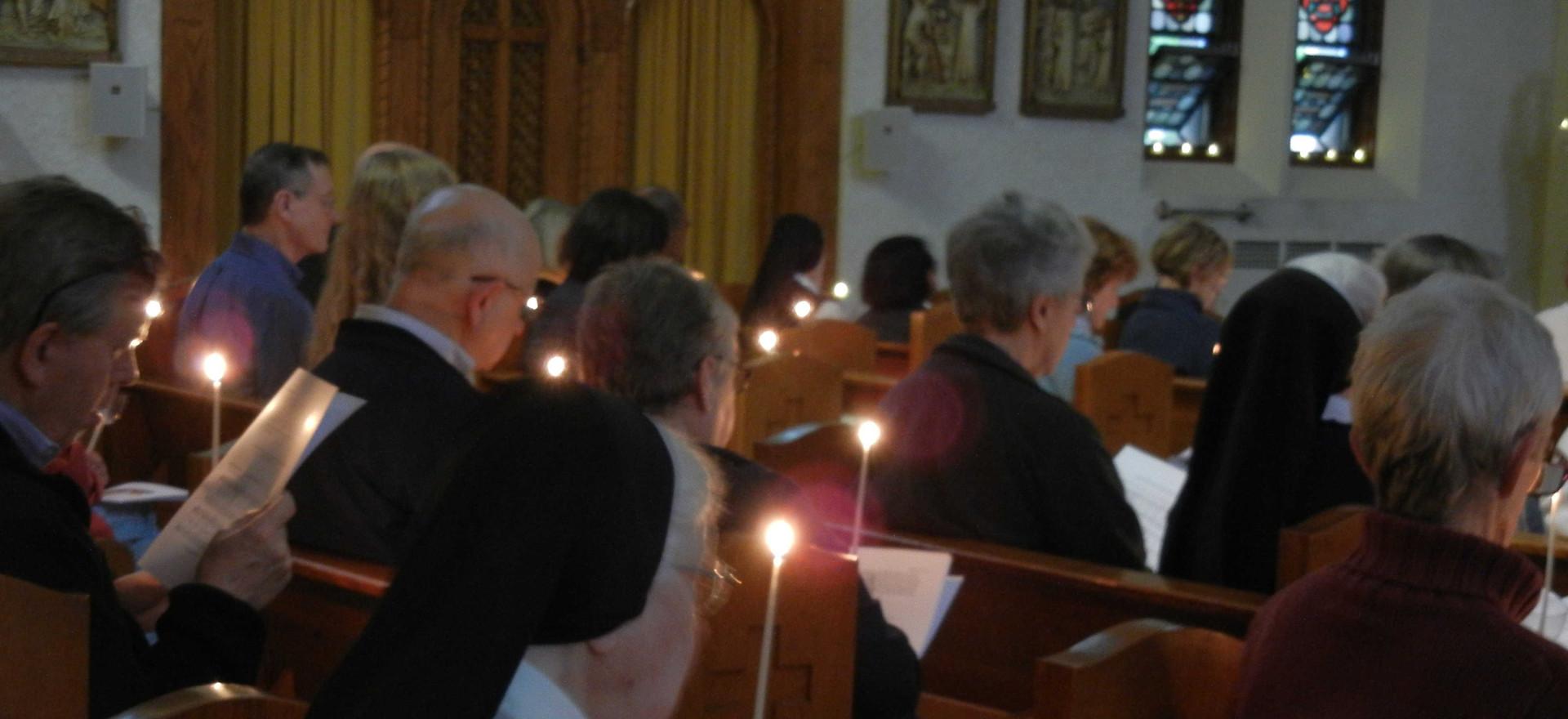 Taizé prayer participants hold lit candles
