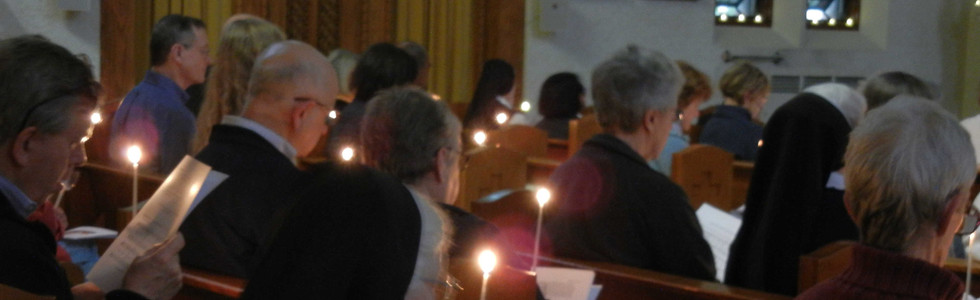 Taizé prayer participants hold lit candles