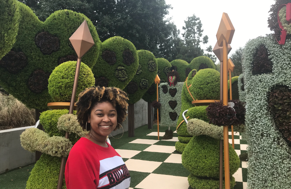 Bri Leigh in front of the Red Queen's court mosaiculture sculptures at the Atlanta Botanical Garden.
