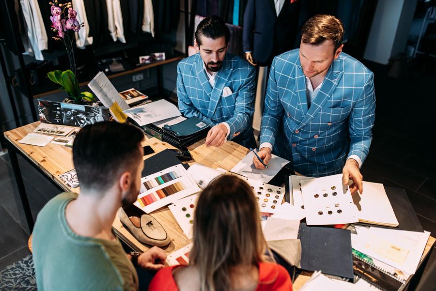 Geschäftsführer und  Schneider im Gespräch mit einem Kundenpaar am Tresen